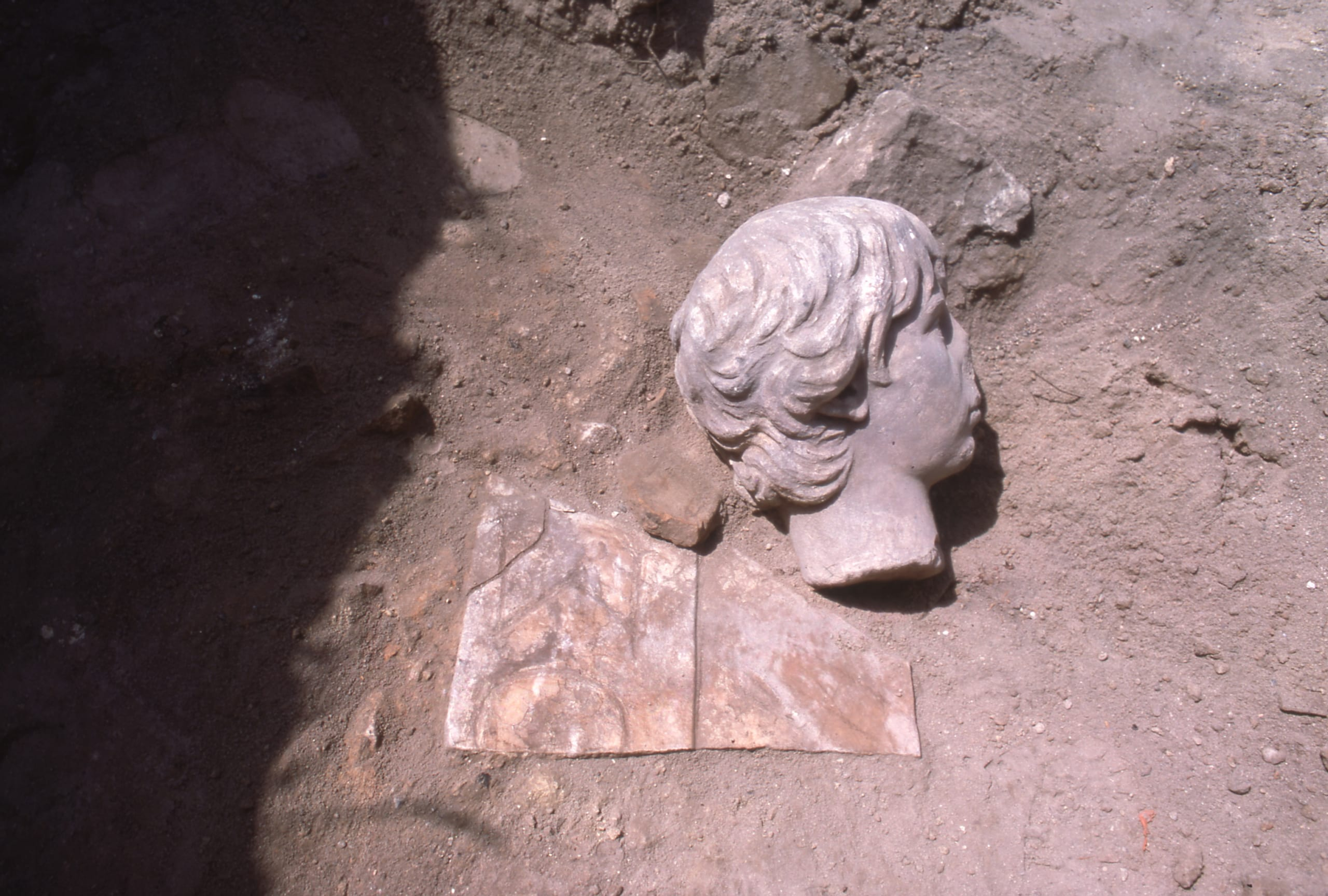 Head of statue and marble fragment